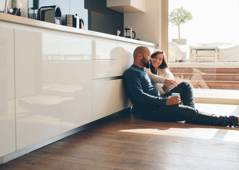 casal sentado no chão da cozinha conversando com as costas apoiadas no móvel planejado branco